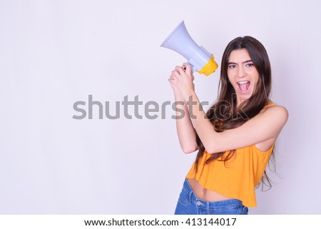 Young beautiful woman shouting through a megaphone or loudspeaker. Caucasian woman expressing. Leadership concept. - stock photo