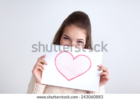 Young beautiful woman showing gift card. Valentine's Day - stock photo