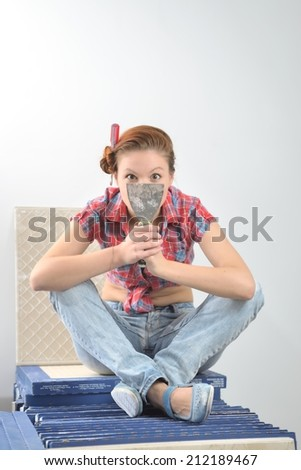 Young beautiful woman sits and plays the fool at the time of repair - stock photo