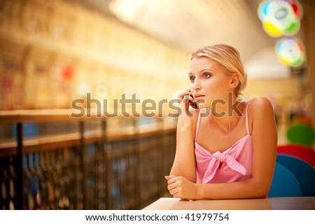 Young beautiful woman sits at table and talks by mobile phone. - stock photo
