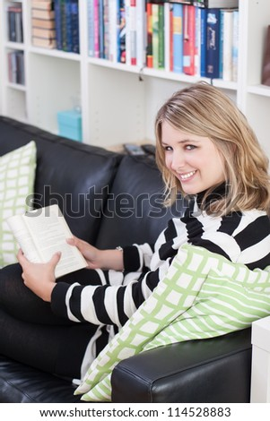 Young, beautiful woman sits on the couch and reads a book at home. A bookshelf is at the background. - stock photo