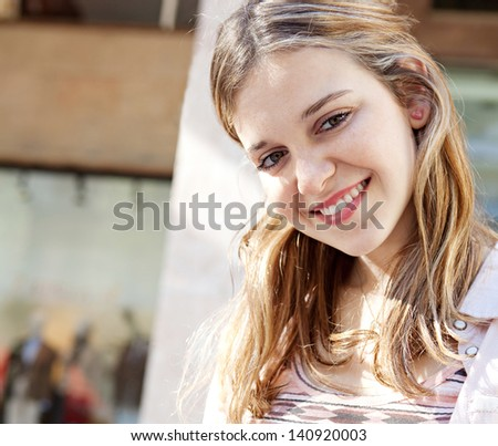 Young beautiful woman sitting on a bench in a city center during a sunny day, using a digital tablet pad near a fashion store, smiling at the camera. - stock photo