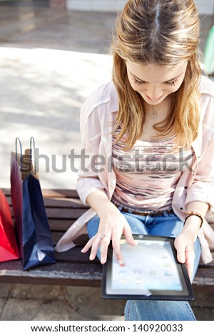 Young beautiful woman sitting on a bench in a city center with her shopping bags during a sunny day, using a digital tablet and smiling. - stock photo