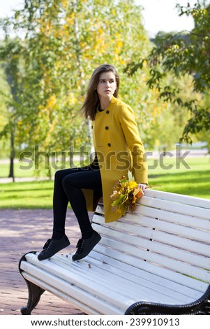 Young beautiful woman sitting on a bench in autumn park - stock photo