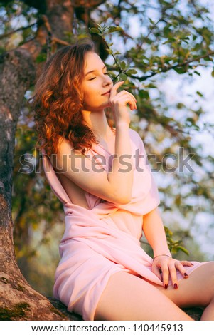 Young beautiful woman sitting on a tree in blooming gardens (selective DOF) - stock photo