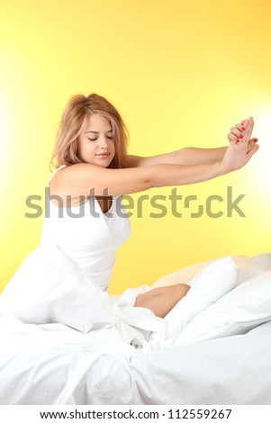 young beautiful woman sitting on bed, on yellow background - stock photo