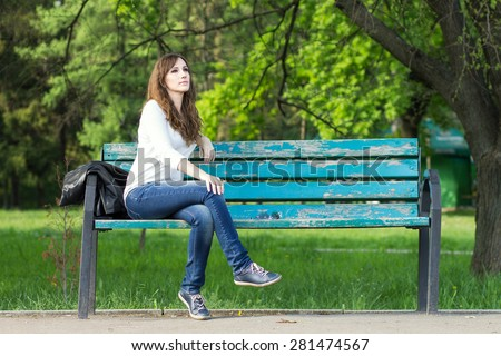Young beautiful woman sitting on bench in park. Pretty girl at outdoors on summer day. Nature environment background. - stock photo