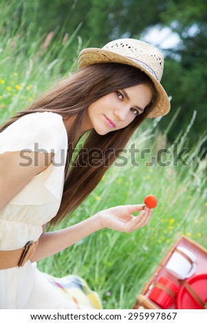 Young beautiful woman sitting on grass and eating strawberries, enjoying summertime. - stock photo