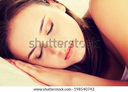 Young beautiful woman sleeping on bed - stock photo