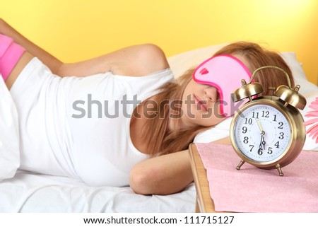 young beautiful woman sleeping on bed with eye mask and  alarm clock, on yellow background - stock photo