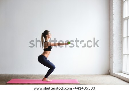 Young beautiful woman squats with dumbbells. - stock photo