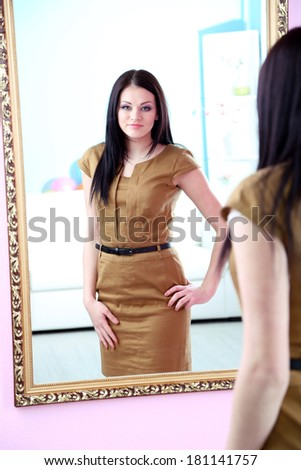 Young beautiful woman standing front of mirror in room - stock photo