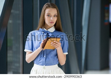 Young beautiful woman standing, looking in the camera. - stock photo