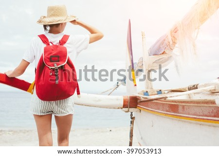 Young beautiful woman standing near sailboat on beautiful island and looking far away (intentional bright sun) - stock photo
