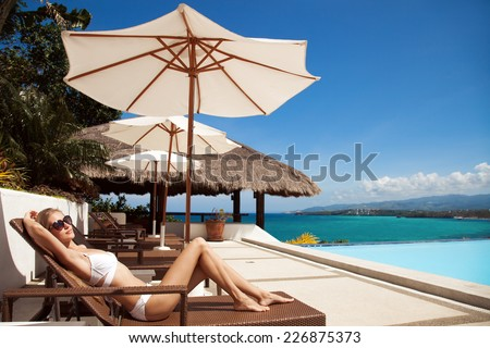 Young beautiful woman sunbathing. Nice sea view. - stock photo