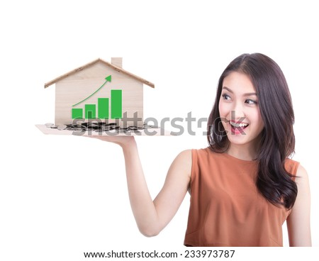 young beautiful woman surprise a house prices high graph on hand - stock photo