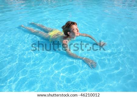young beautiful woman swimming in yellow bikini in paddling pool - stock photo
