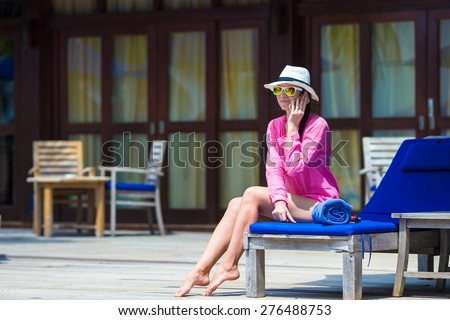 Young beautiful woman talking by phone on white beach - stock photo