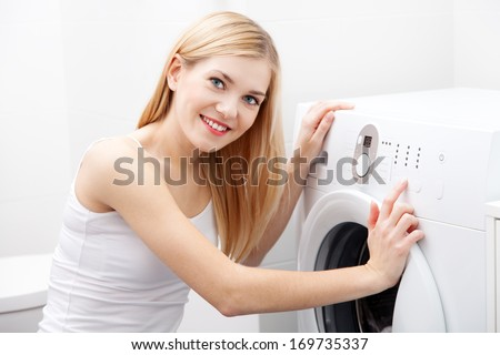 Young beautiful woman using a washing machine - stock photo