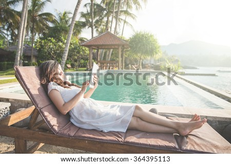 young beautiful woman using tablet while relaxing next to the pool - stock photo