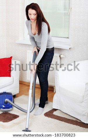 Young beautiful woman using vacuum. Cleaning house conception. - stock photo
