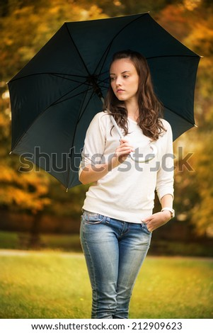 Young beautiful woman walking in rainy autumn park with umbrella. - stock photo