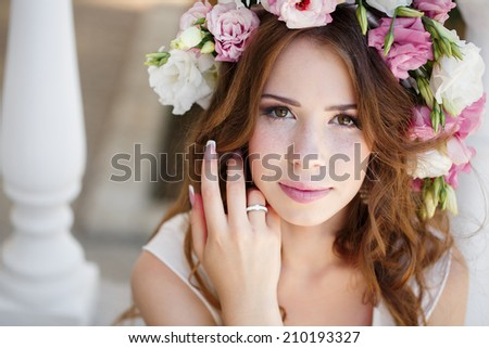 Young beautiful woman walking outdoors at summer. Beautiful young girl in summer field with grain and flower garland. beautiful woman in wreath of flowers - stock photo
