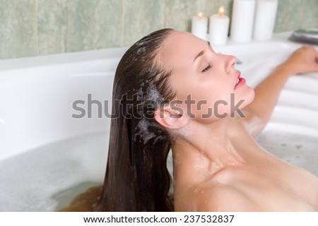 Young beautiful woman washing hair in a bath - stock photo