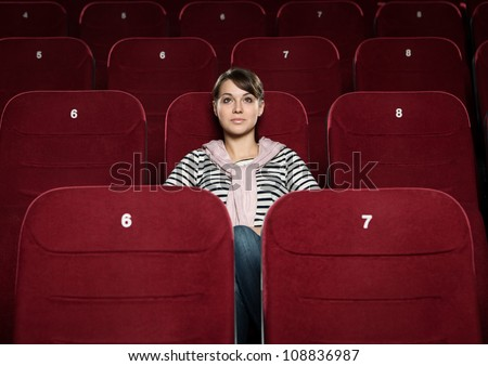 Young beautiful woman watching a movie - stock photo