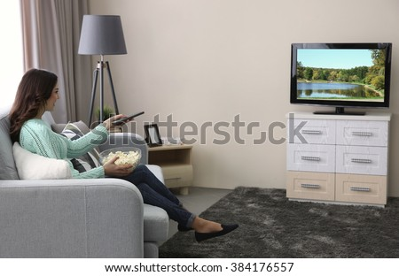 Young beautiful woman watching TV on a sofa at home - stock photo