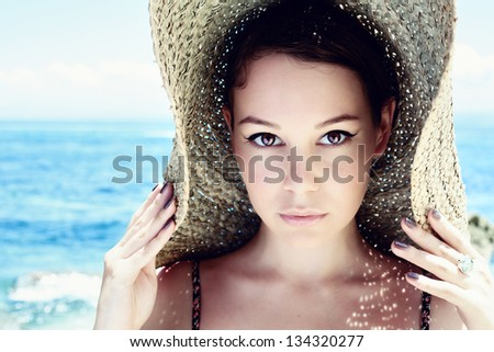 Young, beautiful  woman wearing a straw hat on the beach - stock photo
