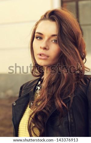 young beautiful woman wearing dress, yellow pullover and leather jacket posing outdoors. stylish fashion portrait - stock photo