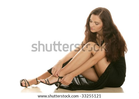 Young beautiful woman wearing high heels sitting isolated on white background - stock photo
