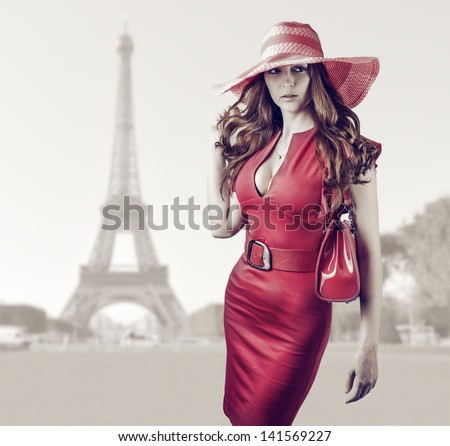 Young beautiful woman wearing sexy red dress, hand bag, belt and hat walking in Paris, France - stock photo