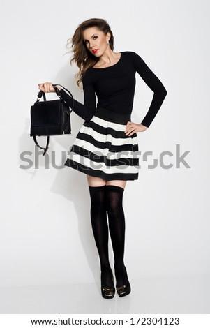 Young, beautiful woman wearing skirt, holding handbag - stock photo