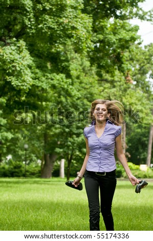 Young beautiful woman wit running in grass barefoot and holding shoes in hands - stock photo