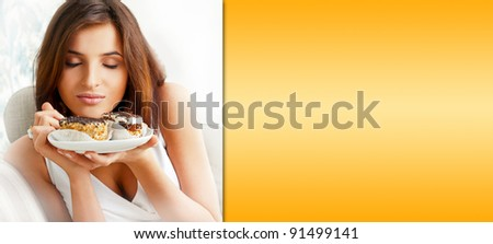 Young beautiful woman with a cake. Closeup portrait. Sitting on sofa at her home. Prepared copyspace at right side of the image - stock photo
