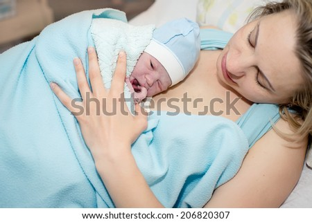Young beautiful woman with a newborn baby after birth - stock photo