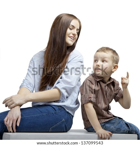 Young beautiful woman with a small boy sitting next to each other. They are talking and watching something. - stock photo
