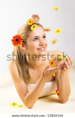 young beautiful woman with a towel and falling flowers - stock photo