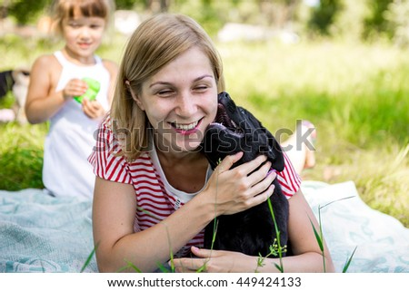 young beautiful woman with a white puppy labrador retrievers. dogs and woman. outdoor portrait. Beautiful woman playing with her dog. - stock photo