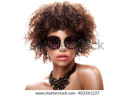 Young beautiful woman with afro posing in fashionable sunglasses and black necklace. Studio shot. - stock photo