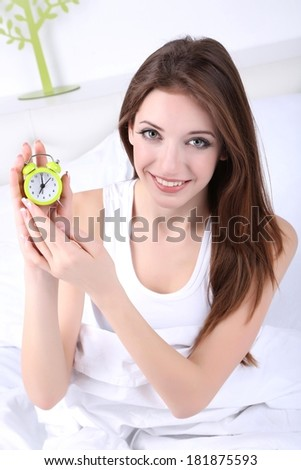 Young beautiful woman with alarm clock in bedroom - stock photo