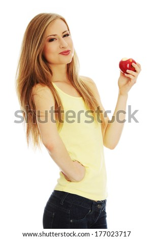 Young beautiful woman with an apple looking towards camera  - stock photo