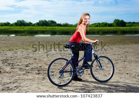 Young beautiful woman with bicycle at the sea - stock photo