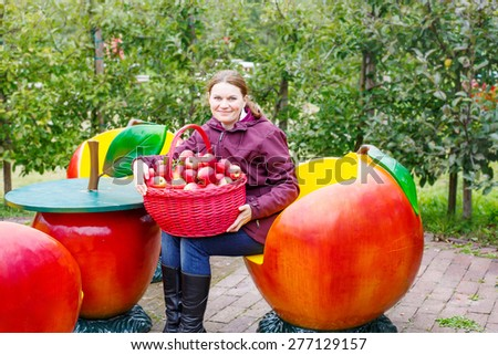 Young beautiful woman with big basket of red organic apples. Harvesting and picking fruits on vegan farm on autumn day, outdoors. - stock photo