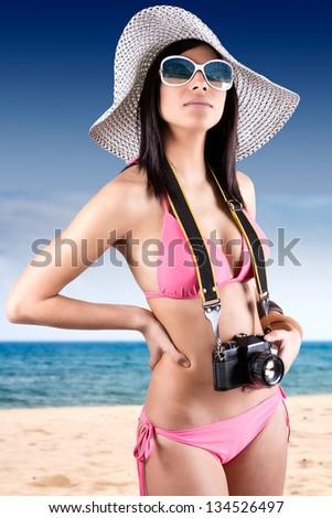 young beautiful woman with bikini holding vintage retro camera - stock photo