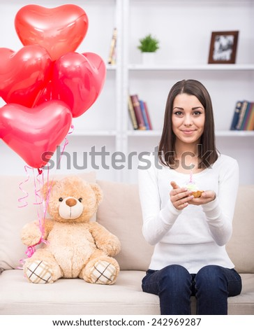 Young beautiful woman with birthday cake. Toy and balloons. - stock photo