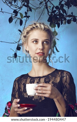 Young beautiful woman with blond hair in braids romantic hairstyle enjoying cup of coffee against blue painted grunge wall  - stock photo