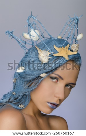 young beautiful woman with blue hair, crown and shells - stock photo